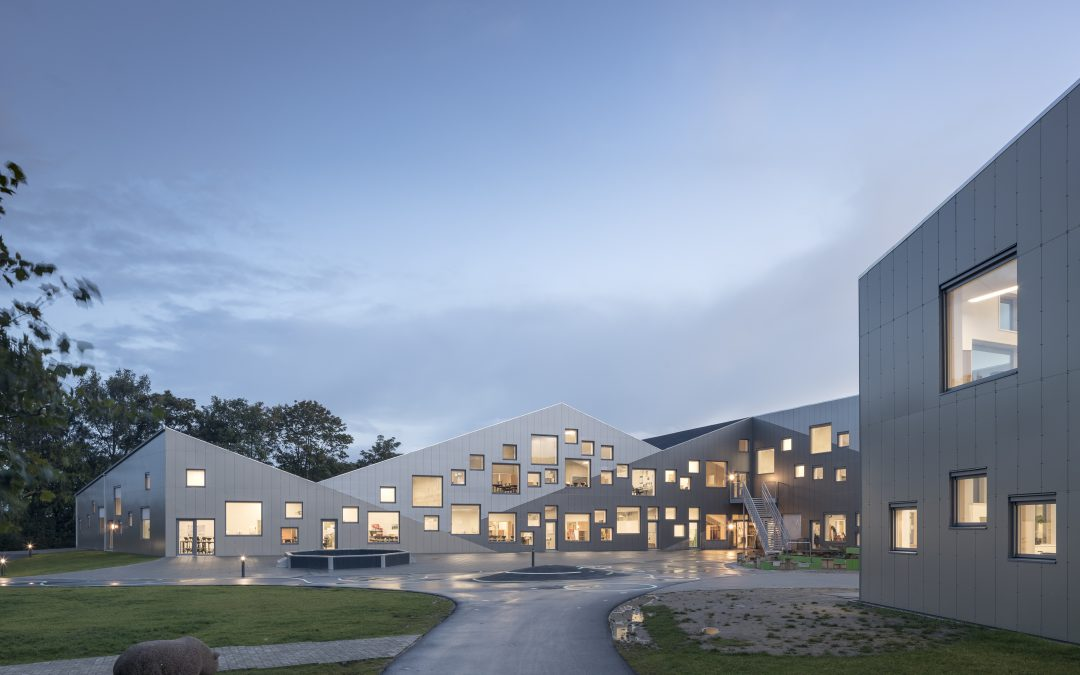A playfully punctured aluminum skin enlivens this Danish school