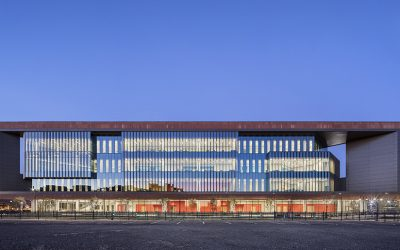 Colored concrete and perforated fins keep this downtown school cool