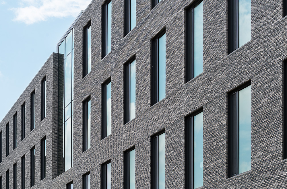 Image of a dark grey brick exterior splashed with windows