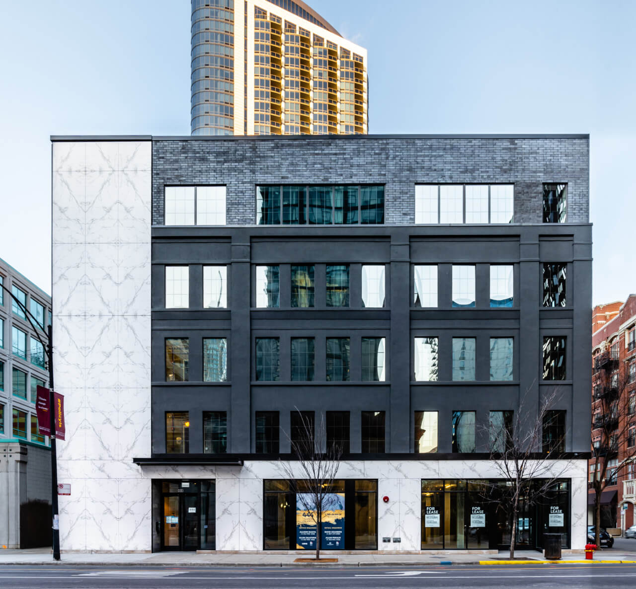 main entrance facade of 444 N Orleans with porcelain stucco and glazed black brick and stucco