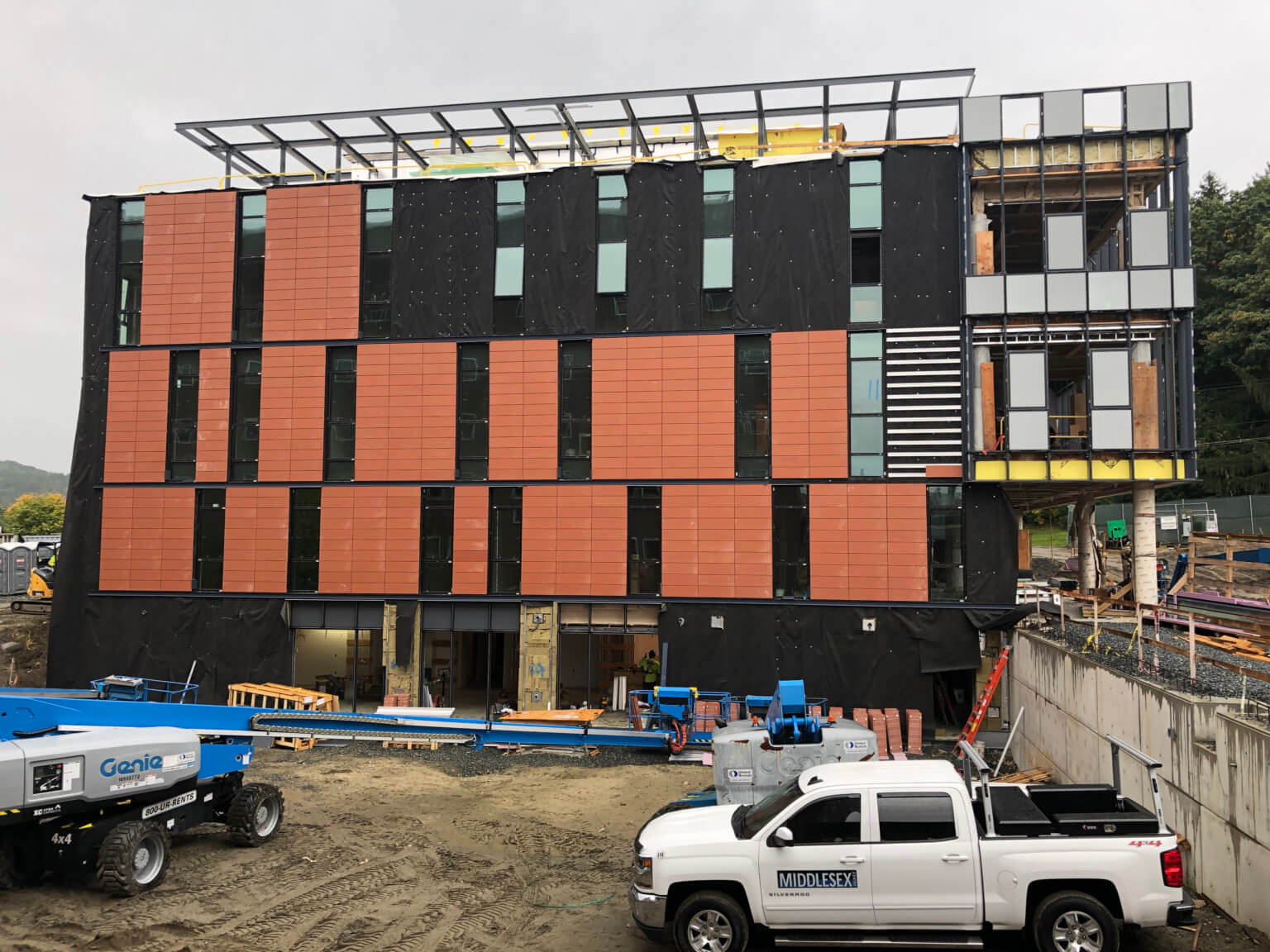 Construction photo of the installation of the thin-tiled terra-cotta panels underway with the partial install of the krypton gas filled triple glazed windows (Courtesy of Leers Weinzapfel Associates)