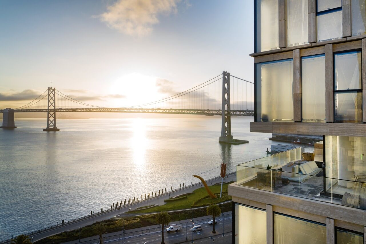 image of side of building with sun on horizon and bridge
