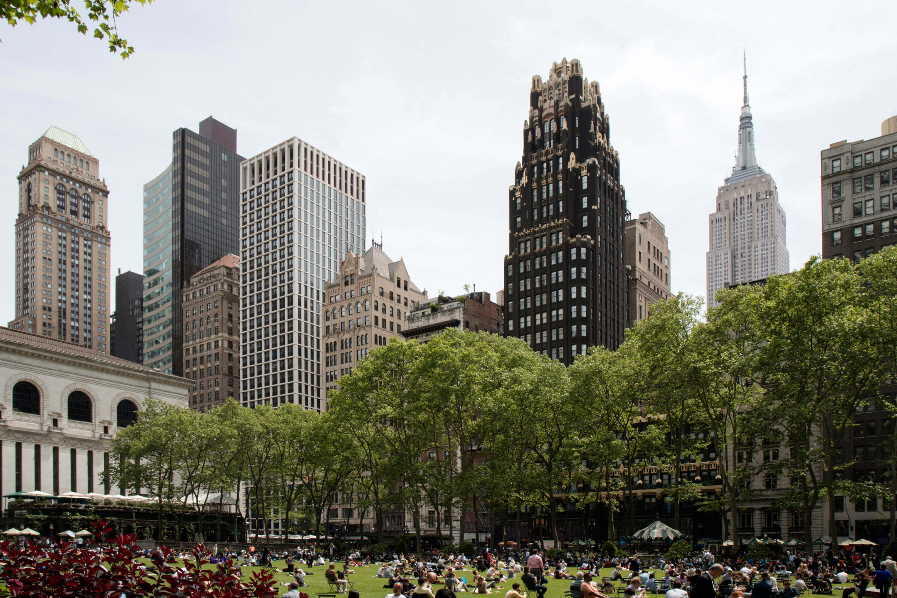 image of several buildings including The Byrant. View is from Bryant Park and includes trees